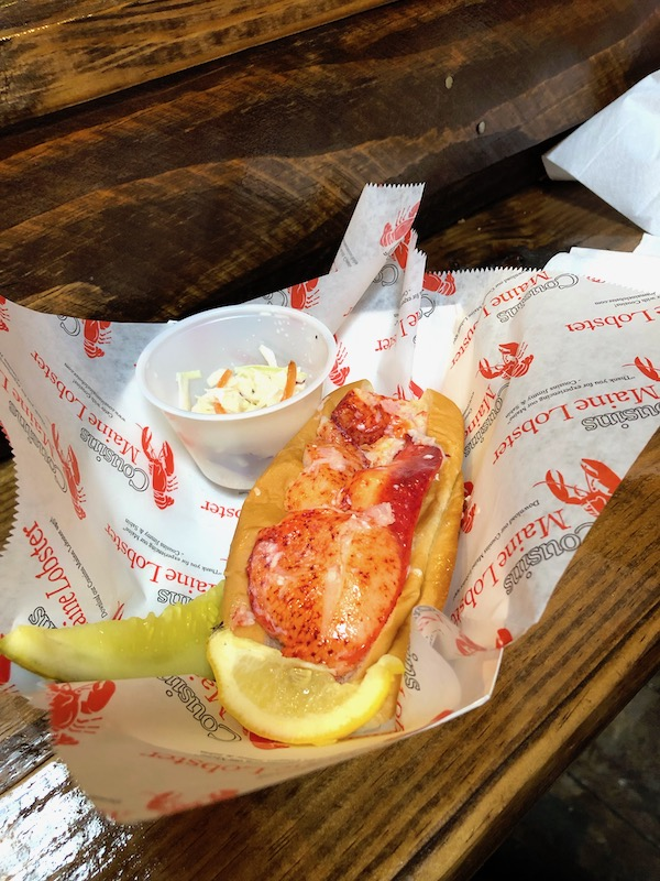 A lobster roll with lemon wedge and pickle spear from Cousins Maine Lobster at the Morgan Street Food Hall.