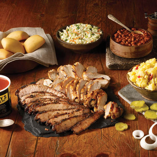 A buffet of food with a large platter of smoked turkey slices on a wood table at Dickey's BBQ Pit Cary NC