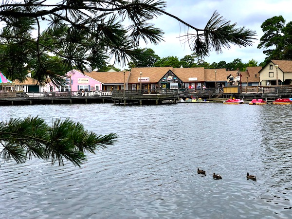 A lake with paddle boats and shops at Historic Smithville NJ.