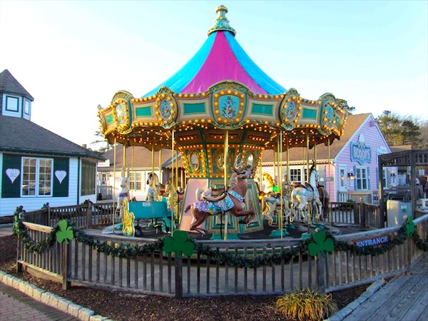 A colorful carousel with hot pink and turquoise top at Historic Smithville NJ