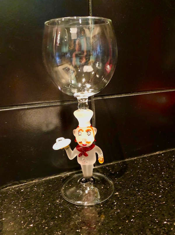 A wine glass with a glass chef for the stem from Historic Smithville NJ sitting on a kitchen counter.