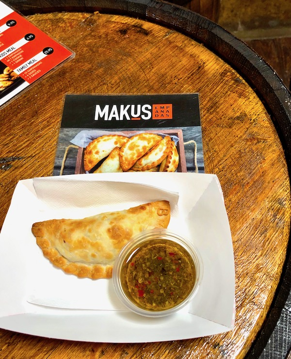 A square white plate topped with an empanada and a small cup of chimichurri at Makus Empanadas at the Morgan Street Food Hall.