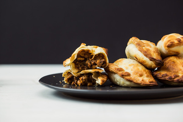 A black plate topped with beef filled empanadas from Makus Empanadas at the Morgan Street Food Hall.