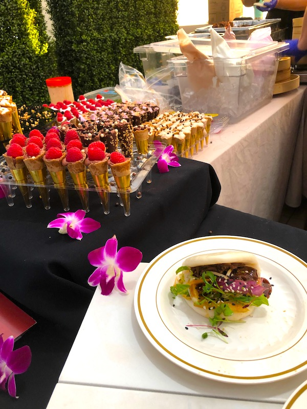 Tiny cones with fruit topping and a plate with a steamed bun filled with meat at the 2019 Flavors Wellington Food and Wine Festival