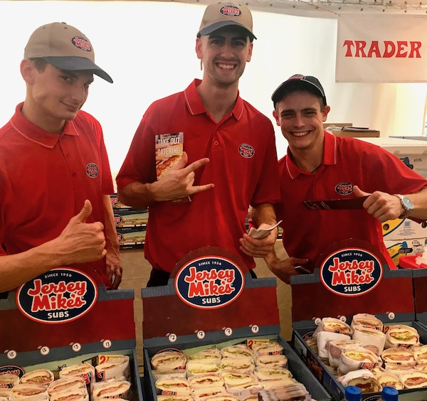 Three guys in red shirts serving trays of sandwiches at the 2019 Flavors Wellington Food and Wine Festival