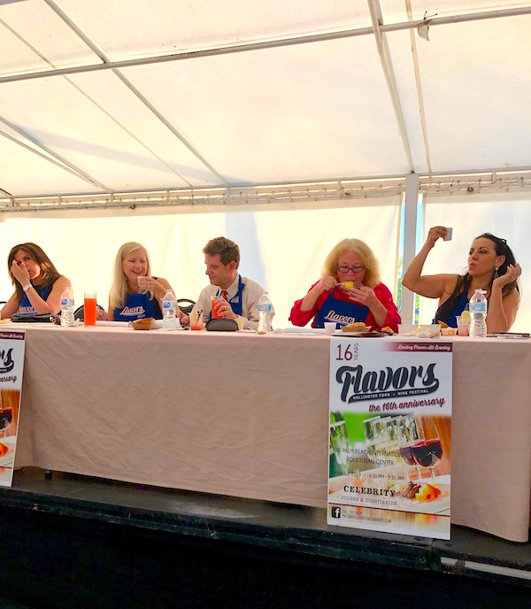 A dais with a group of people tasting food at 2019 Flavors Wellington Food and Wine Festival