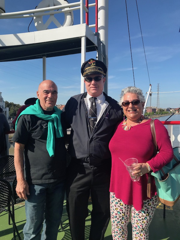 A man and a woman posing with the Captain of our Cruise the Mississippi on the Steamboat Nachez