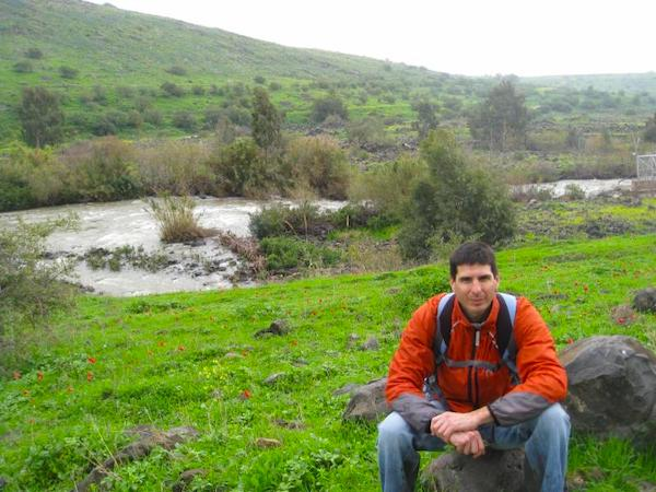 A man crouching with hills and water in the background seeing Israel by Foot.