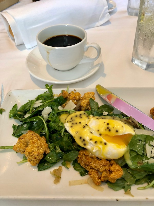 A salad of spinach, poached egg and fried oysters at Jazz Brunch at Commander's Palace