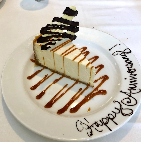 A slice of cheesecake with caramel swiggles and Happy Anniversary written in chocolate on the rim at Jazz Brunch at Commander's Palace
