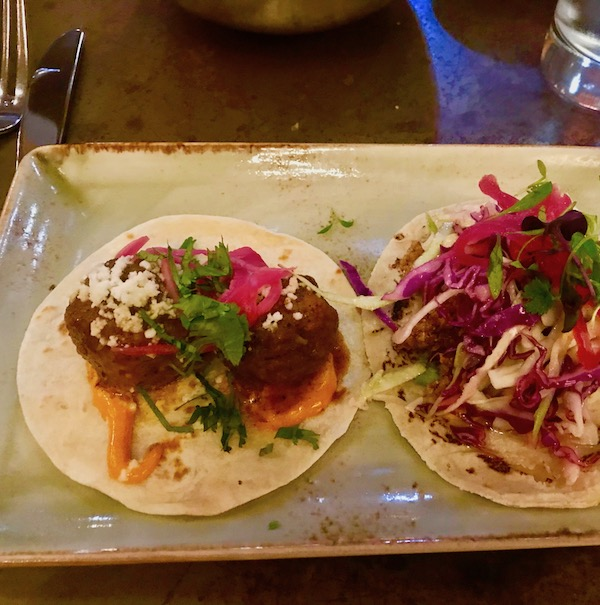 Two tacos on a pale green plate at Johnny Sanchez Mexican Restaurant