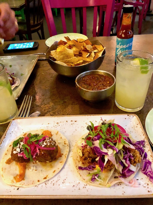 A wood table topped with a plate of tacos, salsa, chips and a margarita at Johnny Sanchez Mexican Restaurant