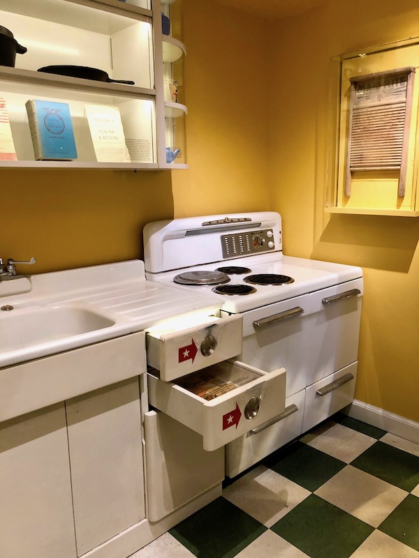 A typical 1940s kitchen on display with electric coil burners on the stove and black and white checkered floor at the National World War II Museum