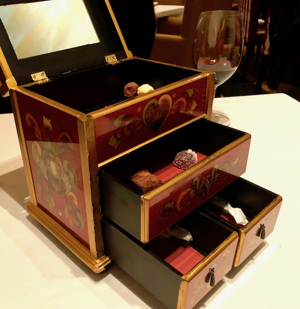 A jewelry box with drawers and lid open holding various candies at Restaurant R'evolution NOLA