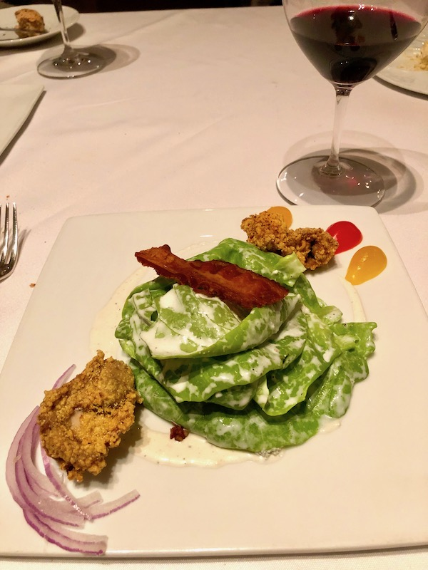 A white plate topped with butter lettuce, crisp bacon, fried oysters and blue cheese dressing at Restaurant R'evolution NOLA