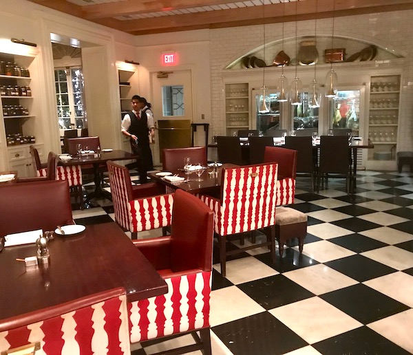 Restaurant R'evolution NOLA casual dining room with red and white upholstered chairs and black and white floor.