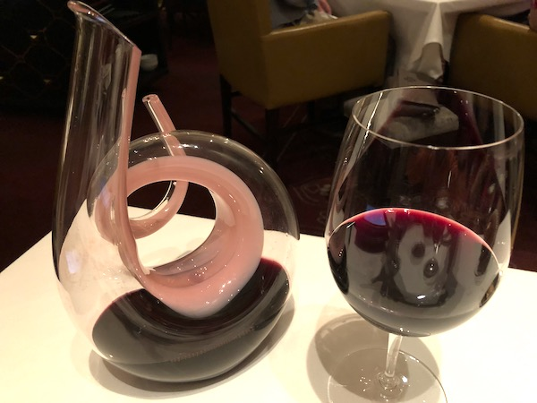 A spiral glass wine decanter with pink swirl next to a glass of red wine at Restaurant R'evolution NOLA.