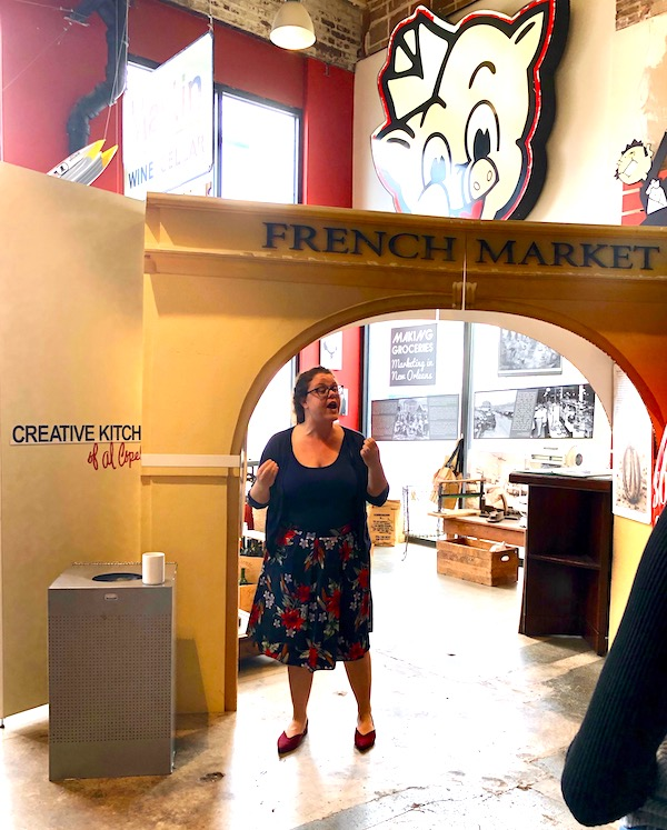 A woman standing under the French Market arch at the Southern Food and Beverage Museum