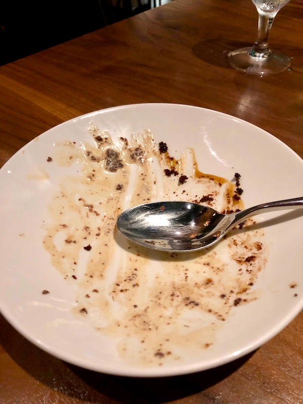 A licked clean dessert plate with a spoon resting on the right at Zasu Restaurant in Mid City New Orleans