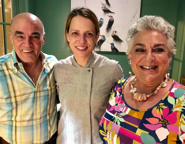 A bald man in a plaid shirt, a female chef in a gray jacket and a silver haired woman in a print top at Zasu Restaurant in Mid City New Orleans