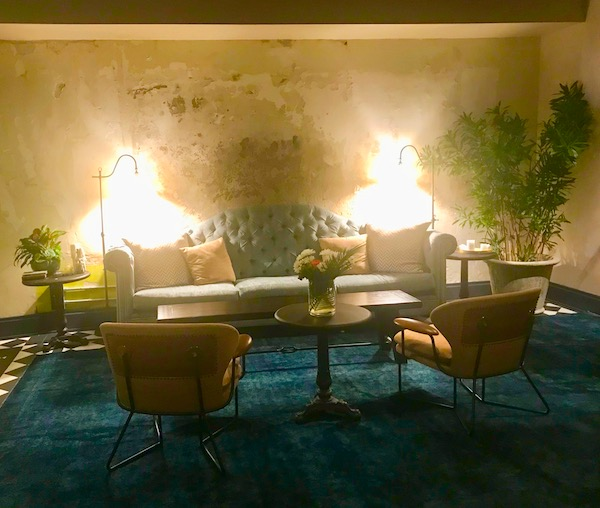 The waiting area of Couvant Bar and Brasserie in New Orleans with safe, chairs, blue area rug and potted plants.