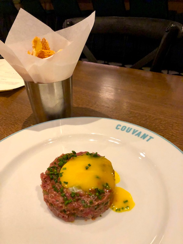 A large white plate topped with steak tartare and an egg yolk with a cone of waffle fries at Couvant Bar and Brasserie in New Orleans.