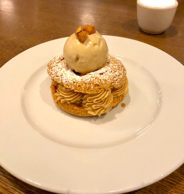 A large cream puff filled with swirls of hazelnut pastry cream and topped with hazelnut ice cream at Couvant Bar and Brasserie in New Orleans