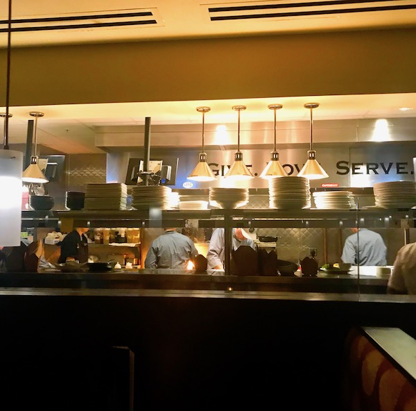 A busy open restaurant kitchen at Harvest Seasonal Grill Delray Beach Florida