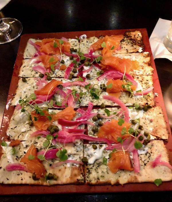 A large rectangular flatbread topped with smoked salmon, red onion slivers, capers and crema at Harvest Seasonal Grill Delray Beach Florida