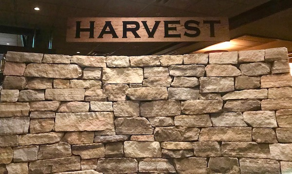 Stone wall with wood sign above that reads Harvest at Harvest Seasonal Grill Delray Beach Florida