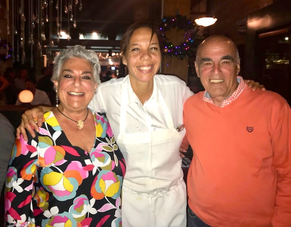 A man and a woman on either side of a chef from our perfect day in New Orleans