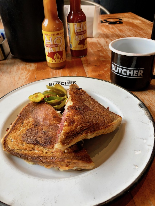 A grilled sandwich on a white plate from Our Perfect Day in New Orleans